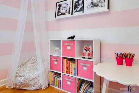 44. Cantinho da leitura para criança decorado em tons de rosa com papel de parede listrado, estante baixa e puff grande redondo – Foto: Gosia Design