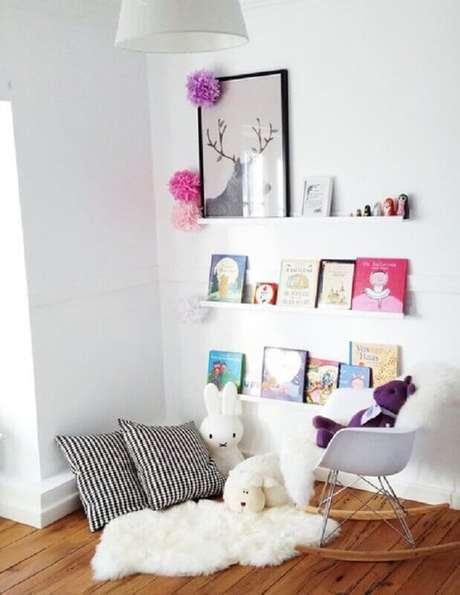 47. Decoração clean em cantinho da leitura para crianças com cadeira de balanço, prateleiras baixas e pequeno tapete branco de pelos – Foto: Mako