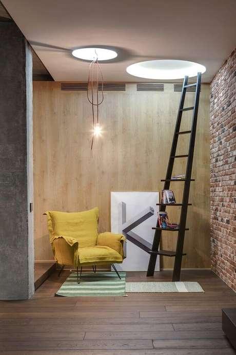65. Escada de madeira como estante para cantinho da leitura com parede de tijolinho e poltrona amarela – Foto: Behance