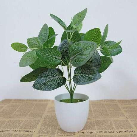 25 – Planta artificial com folhas verdes escuras.