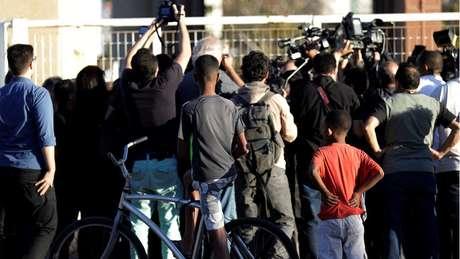 Jornalistas e pedestres observam local em que suspeito de ataque participou de audiência de custódia; candidato do PSL pode ser beneficiado pelo chamado 'efeito de mídia'