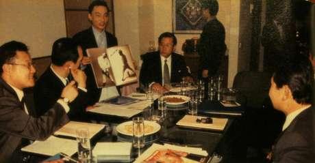 Park, disfarçado de executivo de empresa de publicidade, explicando aos norte-coreanos sobre campanha publicitária: Ele afirma que o hotel em que aparece na imagem costumava ser um lugar para discussão de negócios secretos entre o sul e o norte