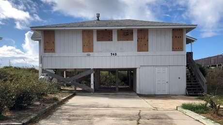 Nas áreas que estão na rota do furacão, população tenta proteger casas usando madeira para reforçar a segurança de portas e janelas