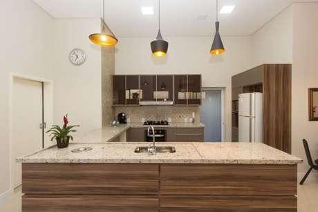 29. Bancada de granito revestida em madeira combinando com os tons escolhidos para a cozinha. Projeto de Engenharia e Arquitetura