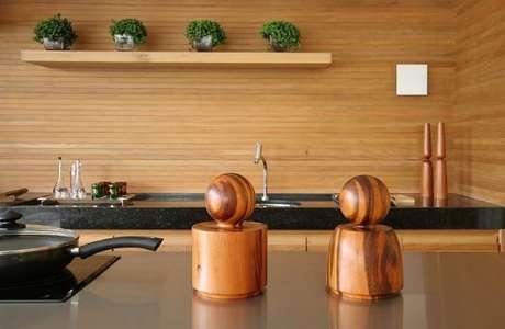 8. Cozinha gourmet revestida em madeira e bancada de granito preto. Projeto de Sandra Picciotto