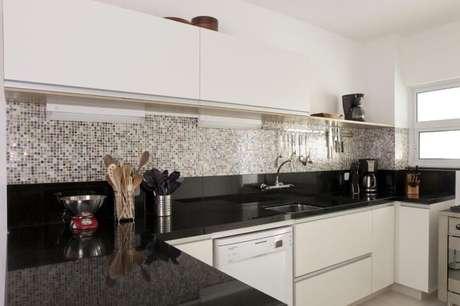 23. Uma boa opção pode ser usar uma bancada escura na cozinha, como nesse projeto de Adelle Porto que usa o granito preto São Gabriel