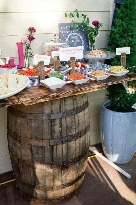 16- A decoração de noivado rústica tem barril como suporte de mesa. Fonte: Garden Decors
