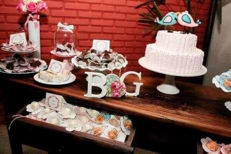 49- O casal de pombinhos sobre o bolo são uma das ideias de decoração de noivado divertidas. Fonte: roofingbrooklyn