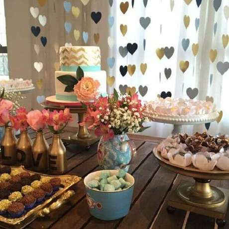 11- A decoração de noivado tem arranjo de corações pendurados atrás da mesa. Fonte: Canal da decoração