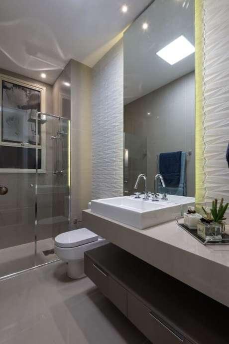 39. Banheiro com revestimento 3D e iluminação embutida atrás do espelho. Projeto de Marie Lauzan