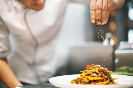 Chef de cozinha usando temperos diferentes para finalizar prato