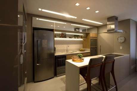 43. Cozinha americana com revestimento 3D em parte da parede com iluminação embutida. Projeto de Marina Turnes