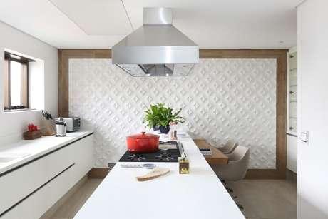 44. Cozinha branca com revestimento 3D em toda a parede com borda de madeira. Projeto de Patricia Bergantin