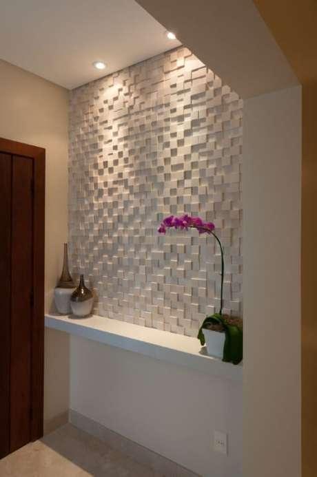 51. Hall com meia parede com revestimento 3D e iluminação focada. Projeto de Bernal Projetos