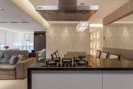 37. A cozinha com ilha ganha arremate da parede com revestimento 3D. Projeto por Raduan Arquitetura.