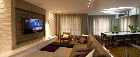 18. O painel claro de revestimento 3D deixa a sala de estar mais larga. Projeto por Ofício da Arte.