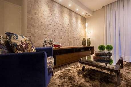 20. A iluminação destaca as pastilhas de revestimento 3D na sala de estar com tapete.