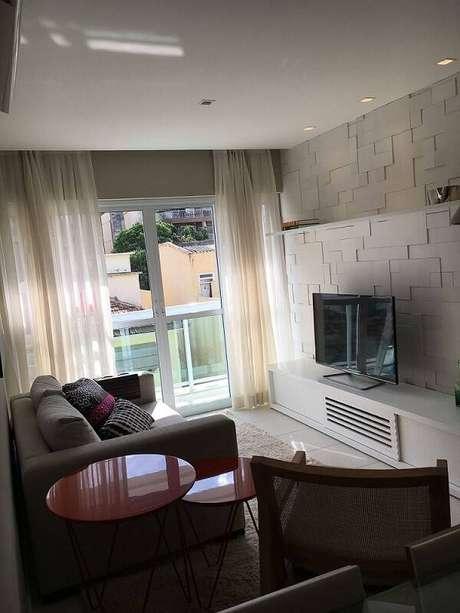 21. A sala de estar com rack baixo tem parede com revestimento 3D. Projeto por Arq Express.