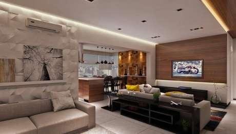 23. A sanca de gesso harmoniza com o revestimento 3D na sala de estar. Projeto por Raduan Arquitetura.