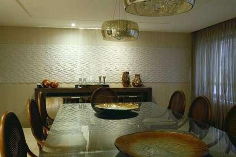 28. Uma faixa de revestimento 3D na sala de jantar traz elegância para o ambiente. Projeto por Celia Beatriz.
