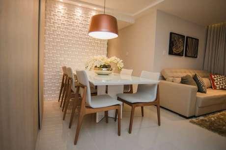 30. A parede da sala de jantar com revestimento 3D combina com a luminária acobreada. Projeto por Andrea Fonseca.