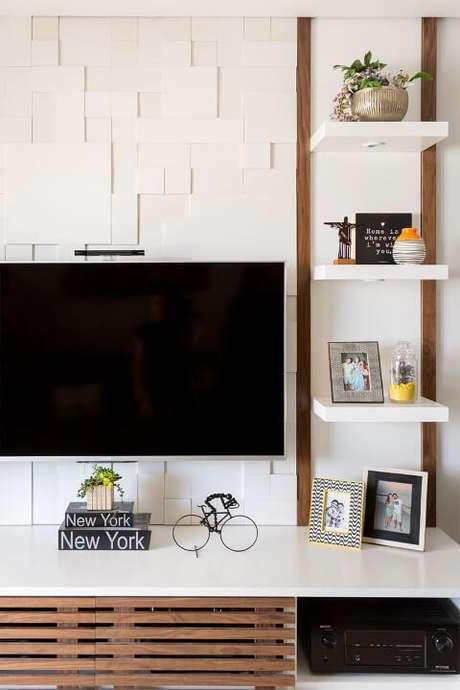 65. Sala com parede com revestimento 3D atrás da TV. Projeto de Bianchi Lima