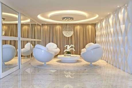 64. Sala de estar clara com parede com revestimento 3D branco. Projeto de Iara Kilaris