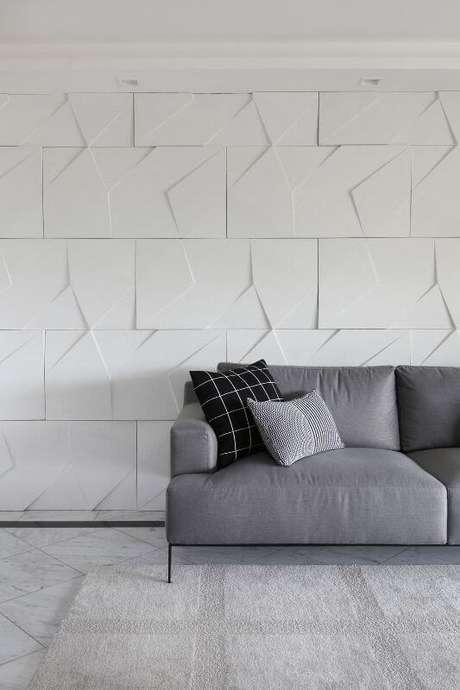 66. Sala de estar com parede com revestimento 3D atrás do sofá. Projeto de Bianchi Lima