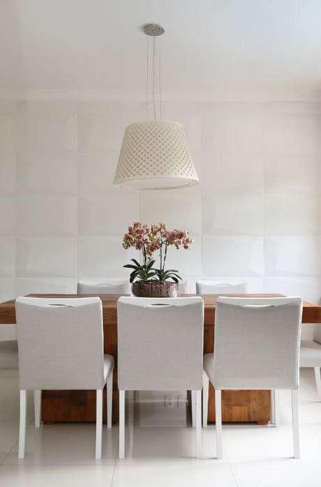 57. Sala de jantar clara com revestimento 3D branco na parede. Projeto de Bianchi Lima