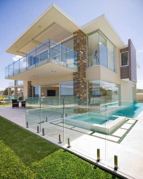 2. Casa moderna com guarda corpo de vidro por toda a sacada e entorno da área de piscina – Foto: Architizer