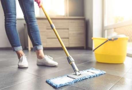 Pessoa limpando o chão com esfregão