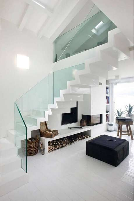 23. Decoração clean e moderna para casa com guarda-corpo de vidro e lareira embaixo da escada – Foto: Pinterest