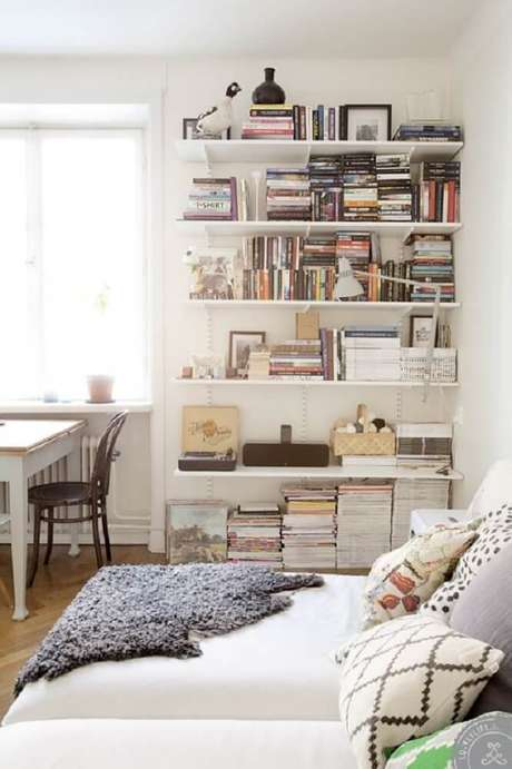28. A decoração do quarto ficou por conta dos livros na prateleira.
