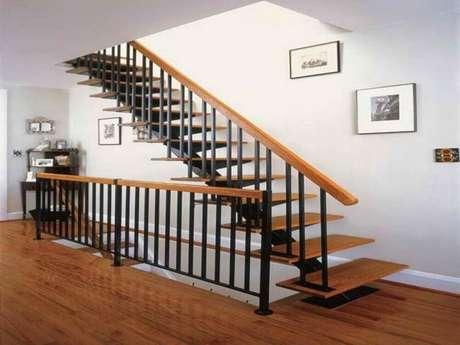 25. Escada de madeira simples com guarda-corpo de ferro preto e corrimão de madeira – Foto: Mathewmitchell Inspirations