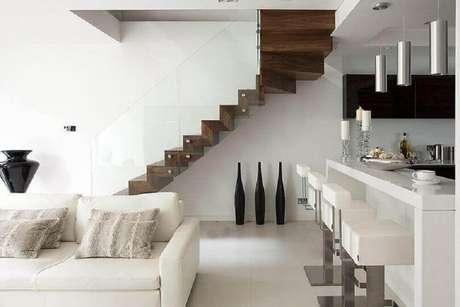 39. Ambiente super moderno com decoração toda branca com guarda-corpo de vidro para escada de madeira escura – Foto: Elite Metalcraft