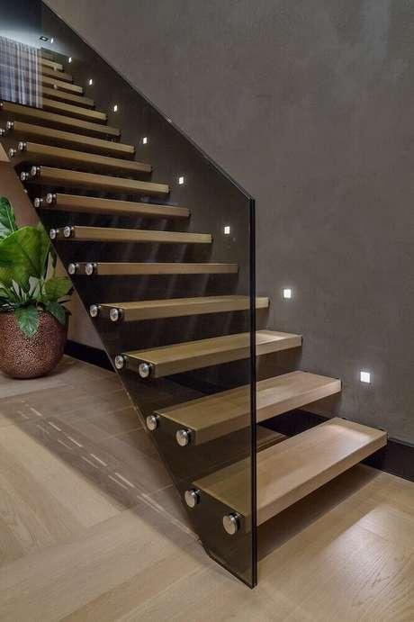 41. Escada de madeira com iluminação embutida próxima aos degraus e guarda-corpo de vidro escuro – Foto: Pinterest
