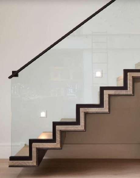 47. Escada com detalhes diferentes, iluminação embutida e guarda-corpo de vidro com corrimão de alumínio – Foto: Deavita