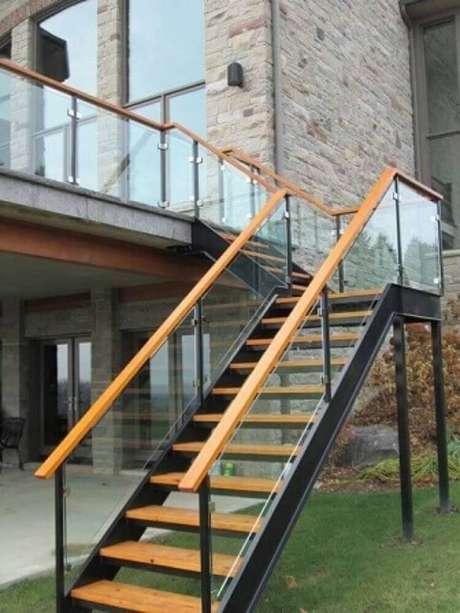 50. Área externa com escada de madeira e guarda-corpo de vidro – Foto: Roofing Brooklyn