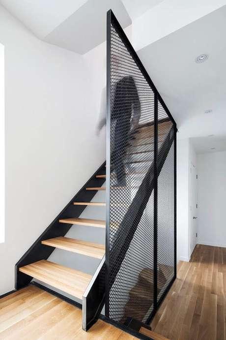 59. Ambiente com estilo moderno com escada de madeira e guarda-corpo feito com uma grade de ferro pintado de preto – Foto: ArchDaily