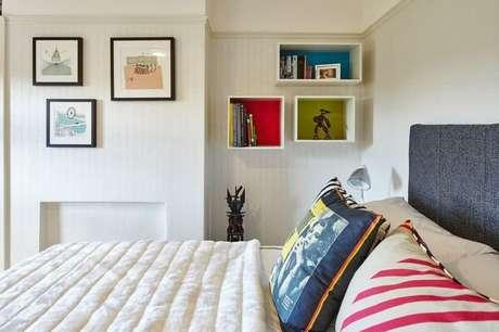 18. O quarto com decoração clean ganhou mais personalidade com as prateleiras coloridas.
