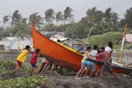 Filipinos tentam colocar barco em local seguro antes da chegada do tufão Mangkhut, em Aparri