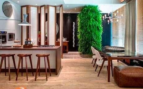 41- A parede verde de samambaia no fundo da sala compõe a decoração. Fonte: Ana Camila Vieira