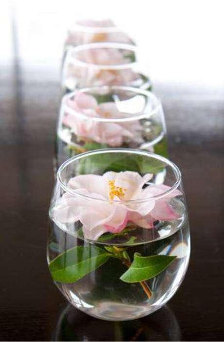 13. Flores em copos são baratas e funcionam como centro de mesa na decoração de festa.