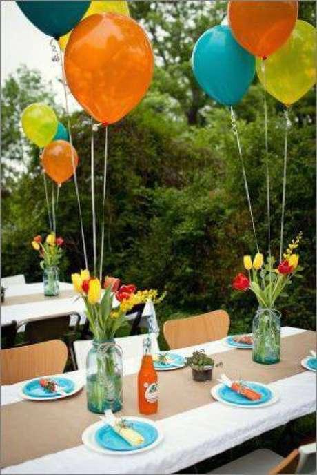 24. Decoração de festa com centros de mesa com potes e bexigas amarradas.