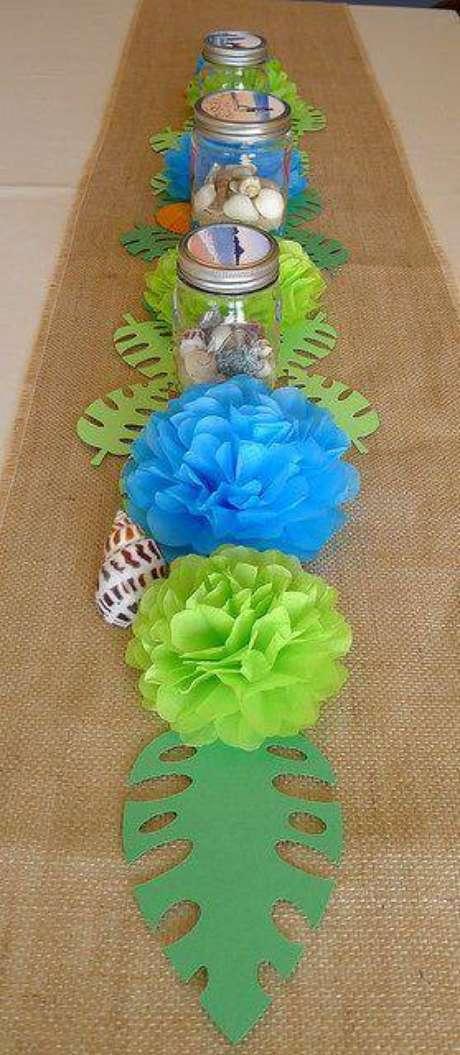26. Decoração de festa com tecido rústico, flores e folhas de papel.