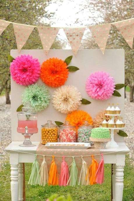 29. A decoração de festa com flores e enfeites de papel fica bonita e colorida.