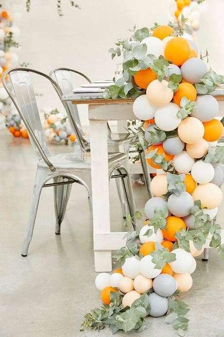 30. Bexigas são baratas e incrementam a decoração de festa. Use flores e folhas para embelezar ainda mais.