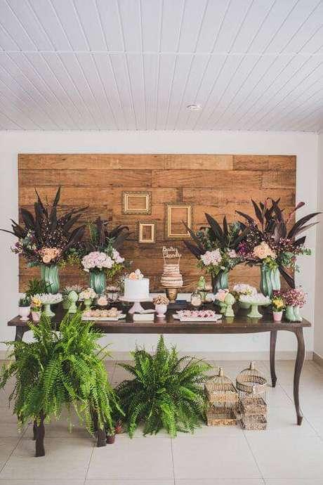 41. Uma mesa mais elegante é possível com madeira, flores e folhagens na decoração de festa.