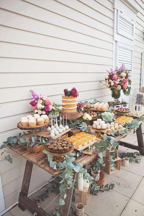 44. As folhas na decoração de festa rústica preenchem a mesa do bolo.