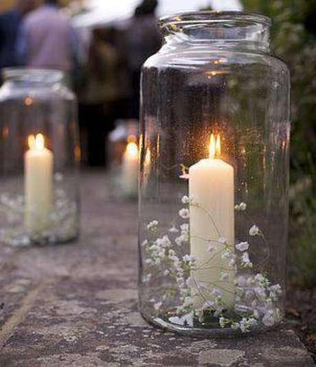 50. Os potes com velas e flores delicadas viram lindas lanternais, ideais para festas noturnas.